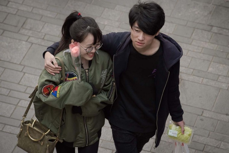 A couple walks at a shopping mall on Valentine's Day in Beijing on February 14, 2017. (NICOLAS ASFOURI/AFP/Getty Images)