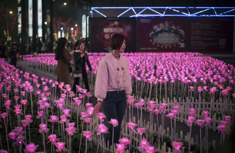 A woman poses in the middle of a display of lit flowers during Valentine's Day on a street in Beijing on February 14, 2017. A Pakistani court has banned public celebrations of Valentine's Day in the capital Islamabad while Indonesian students plan to spurn the event, as the festival of love gets a chilly reception in parts of Asia. (FRED DUFOUR/AFP/Getty Images)