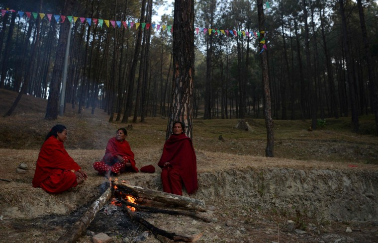 Nepalese Hindu devotees warm themselves beside a fire as they arrive for a mass bathing ritual during the month-long Swasthani Festival in Changu Narayan at Bhaktapur, on the outskirts of Kathmandu on February 8, 2017. Hundreds of married and unmarried women in the Himalayan nation are marking the month-long fast in the hope of a prosperous life and conjugal happiness. (Prakash Mathema/AFP/Getty Images)