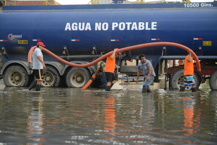 Municipal workers use a water truck to remove stagnant water from a neighborhood in the city of Chiclayo, some 700 kilometers north of Lima, Peru, on February 6, 2017. Torrential rains, landslides and overflowing of rivers have killed 25 people and affected over 200,000 in Peru since the beginning of the year. (Cris Bouroncle/AFP/Getty Images)