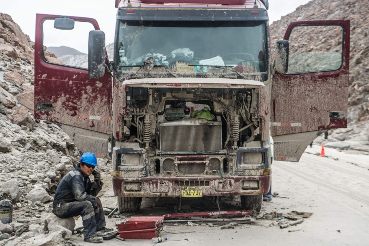A man sits next to a truck at the Peruvian Panamerican highway after a landslide in Arequipa, southern Peru, on January 27, 2017. Floods and landslides in Peru have killed four people and displaced more than 11,000 families over recent weeks, the authorities said Friday. Three people drowned when their vehicle was caught in a flood in the southern Arequipa region, the National Civil Defense Institute said. (Ernesto Benavides/AFP/Getty Images)