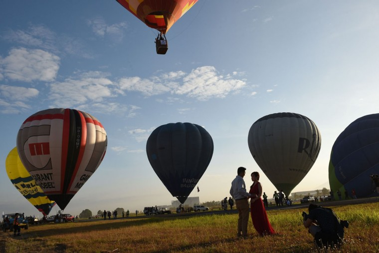 A couple poses for their pre-nuptial photo session in front of balloons taking flight during the annual International Hot Air Balloon Festival at the former Clark US Air Force base in Pampanga province, north of Manila on February 9, 2017. Some 29 balloon enthusiasts from around the globe are participating in the event which runs February 9 to 12. (TED ALJIBE/AFP/Getty Images )