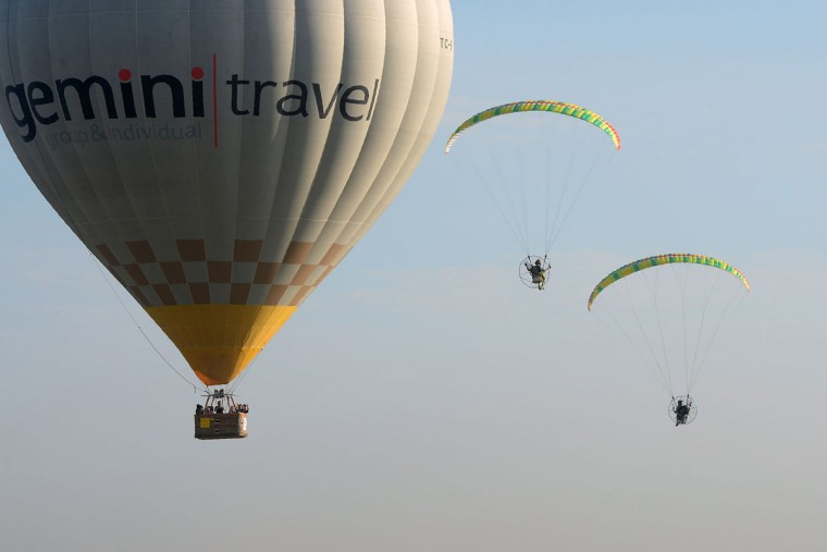 Powered paragliders are seen in flight past a balloon during the annual International Hot Air Balloon Festival at the former Clark US Air Force base in Pampanga province, north of Manila on February 9, 2017. Some 29 balloon enthusiasts from around the globe are participating in the event which runs February 9 to 12. (TED ALJIBE/AFP/Getty Images)