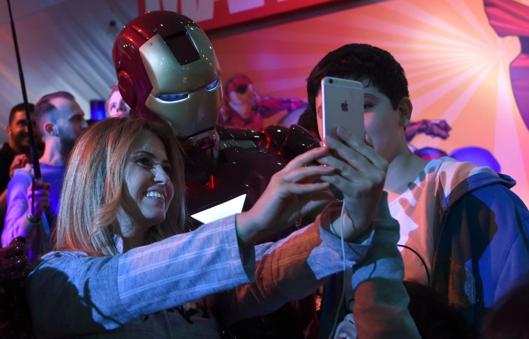 """A Lebanese woman poses for a selfie with a man dressed up as """"Iron Man"""" during the country's first ever Comic-Con event in the coastal city of Jeddah on February 16, 2017. The three-day festival of anime, pop art, video gaming and film-related events is part of a government initiative to bring more entertainment to Saudi Arabia which bans alcohol, public cinemas and theatre. (Fayez Nureldine/AFP/Getty Images)"""