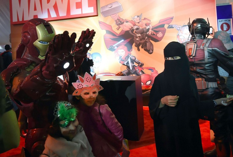 """A Saudi woman looks on as children pose for a photo with a man dressed up as """"Iron Man"""" during the country's first ever Comic-Con event in the coastal city of Jeddah on February 16, 2017. The three-day festival of anime, pop art, video gaming and film-related events is part of a government initiative to bring more entertainment to Saudi Arabia which bans alcohol, public cinemas and theatre. (Fayez Nureldine/AFP/Getty Images)"""