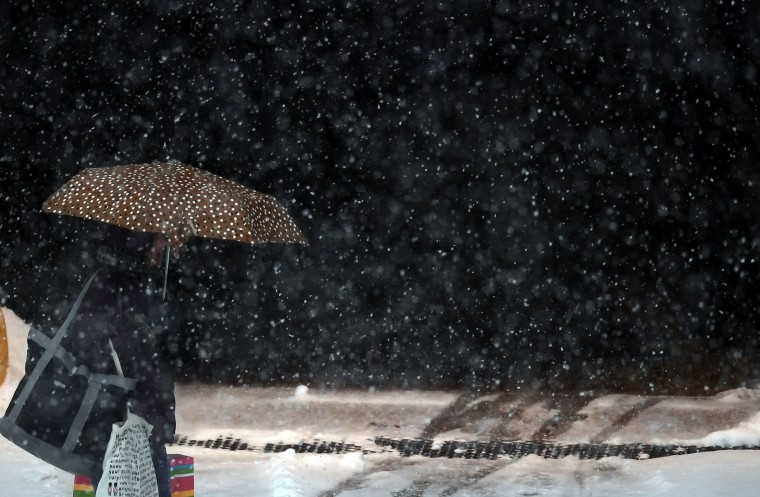 A woman uses an umbrella as she makes her way during snow fall in New York on January 7, 2017. (Jewel Samad/AFP/Getty Images)