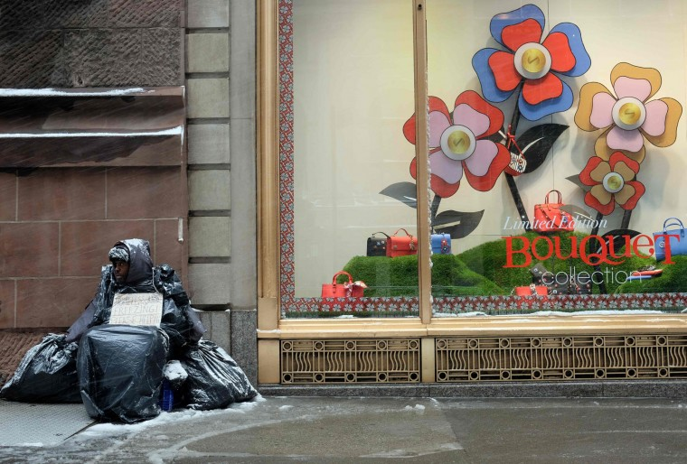 A man covers himself with plastic sheets as he begs for money during a winter storm in New York on February 9, 2017. A heavy winter snow storm lashed the northeastern United States Thursday, subjecting New York to near blizzard-like conditions and forcing flight cancellations as schools and the United Nations closed. (Jewel Samad/AFP/Getty Images)