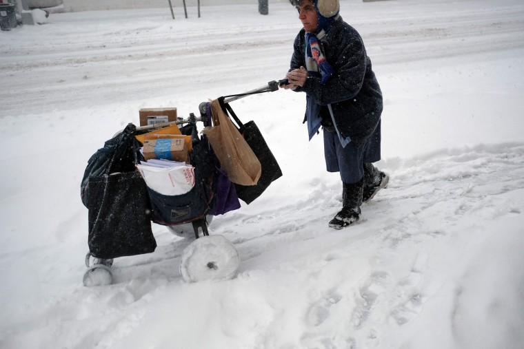 A postwoman pushes her mail cart on a snow-covered street during a winter storm in New York on February 9, 2017. A heavy winter snow storm lashed the northeastern United States Thursday, subjecting New York to near blizzard-like conditions and forcing flight cancellations as schools and the United Nations closed. (Jewel Samad/AFP/Getty Images)