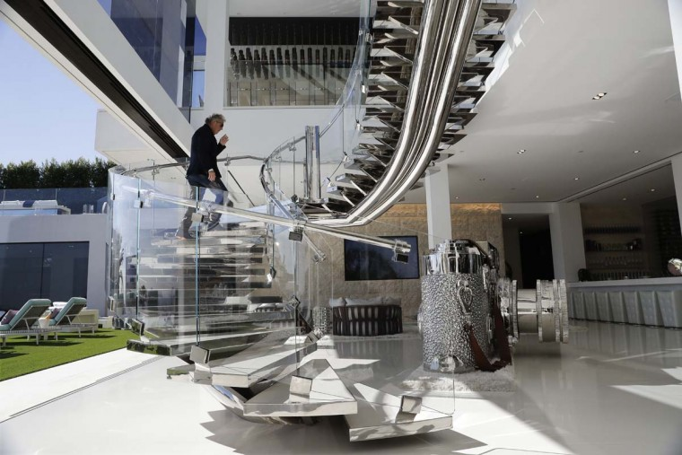 In this Thursday, Jan. 26, 2017, photo, developer Bruce Makowsky walks up the handcrafted steel staircase next to a large sculpture of a Leica camera at a $250 million mansion he built in the Bel-Air area of Los Angeles. The mansion includes 12 bedroom suites, 21 bathrooms, five bars, three gourmet kitchens, a spa and an 85-foot infinity swimming pool with stunning views of Los Angeles. (AP Photo/Jae C. Hong)