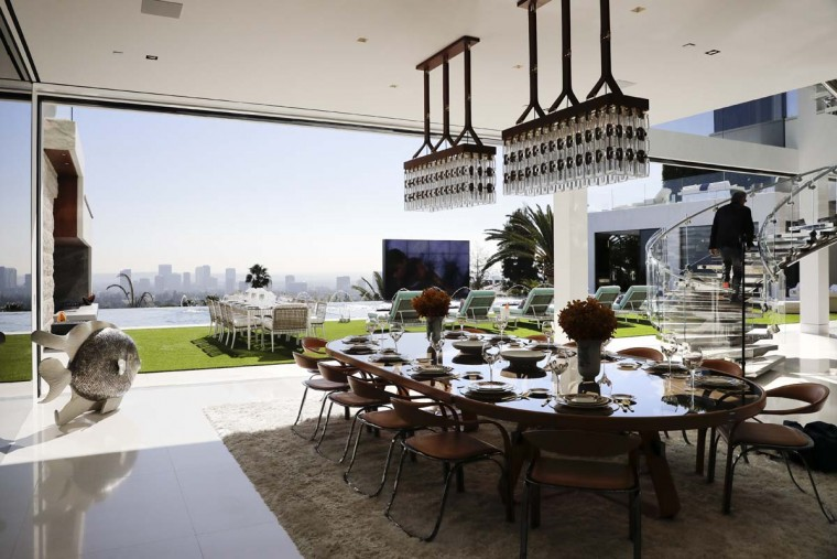 This Thursday, Jan. 26, 2017, photo shows the indoor and outdoor dining areas at a $250 million mansion in the Bel-Air area of Los Angeles. The mansion, the most expensive home listed in the U.S., includes 12 bedroom suites, 21 bathrooms, five bars, three gourmet kitchens, a spa and an 85-foot infinity swimming pool with stunning views of Los Angeles. (AP Photo/Jae C. Hong)