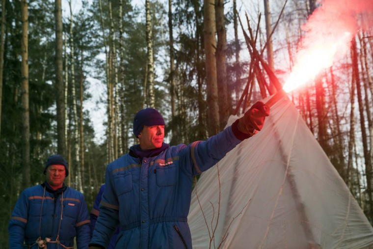 NASA astronaut Andrew J. Feustel holds a flare as Russian Cosmonaut Oleg Artemyev, left, stands near the hut which they built during a three-day winter training in a forest at Russian Space Training Center in Star City, outside Moscow, Russia, Wednesday, Feb. 8, 2017. The three are being trained for a future mission to the International Space Station. (AP Photo/Pavel Golovkin)