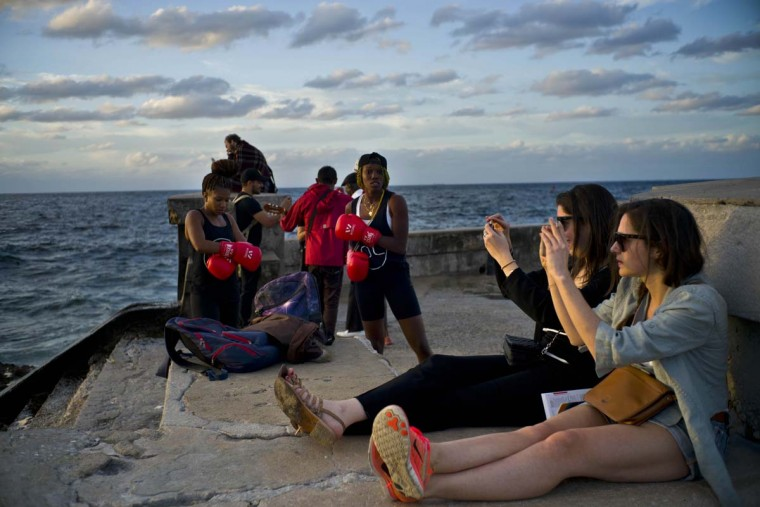 In this Jan. 30, 2017 photo, boxers Idamerys Moreno, left, and Legnis Cala, get ready for a photo session, as tourists take photos of the sunset, on Havana's sea wall in Cuba. Female athletes in Cuba have made strides in many other sports, including wrestling, judo and most recently, weightlifting, but not in boxing. (AP Photo/Ramon Espinosa)
