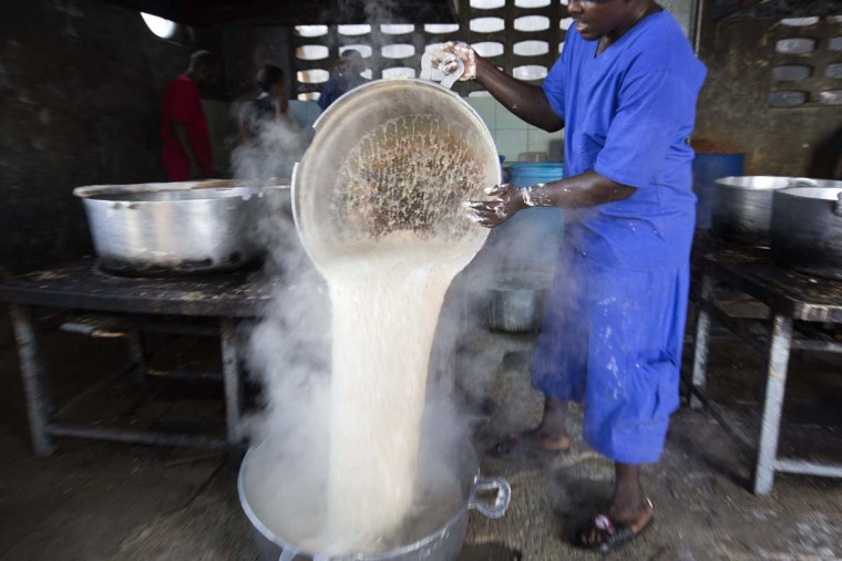 In this Feb. 13, 2017 photo, a prisoner pours hot oatmeal into a a large stock pot in the kitchen of the National Penitentiary in downtown Port-au-Prince, Haiti. Some inmates are provided meals by visiting relatives but the majority of prisoners are dependent on authorities to feed them twice a day and get little more than rationed supplies of rice, oats or cornmeal. (AP Photo/Dieu Nalio Chery)