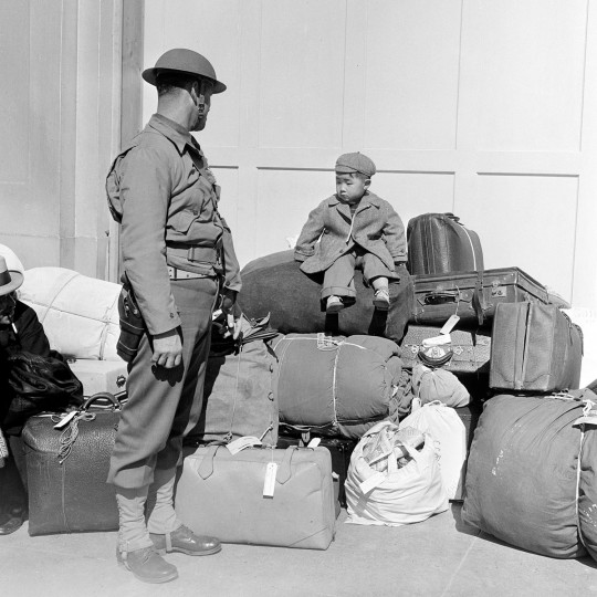 In this April 6, 1942 file photo, a boy sits on a pile of baggage as he waits for his parents, as a military policeman watches in San Francisco. More than 650 citizens of Japanese ancestry were evacuated from their homes and sent to Santa Anita racetrack, an assembly center for war relocation of alien and American-born Japanese civilians. (AP Photo)