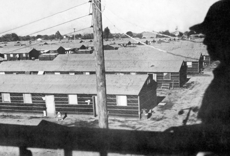 In this undated photo provided by the War Relocation Authority, armed guard overlooks barracks built in the middle of the racetrack at the Fresno Fairgrounds in Fresno, Calif. The assembly center, one of 13 built in Calif., was the first stop for detainees before they were sent to permanent internment camps. About 5,300 people were held at the center between May and October 1942. (AP photo/War Relocation Authority)