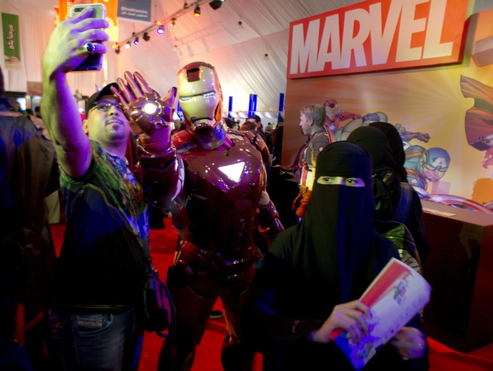 """Visitors pose with a man wearing as the """"Iron Man"""", a fictional superhero appearing in American comic books published by Marvel Comics, during the Saudi Comic Con (SCC) which is the first event of its kind to be held in Jiddah, Saudi Arabia, Thursday, Feb. 16, 2017. (AP Photo)"""