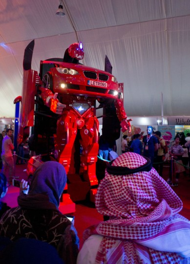 """Visitors watch the Turkish made robot """"Letrons"""", as it morphs from a car to a giant robot during the Saudi Comic Con (SCC) which is the first event of its kind to be held in Jiddah, Saudi Arabia, Friday, Feb. 17, 2017. (AP Photo)"""