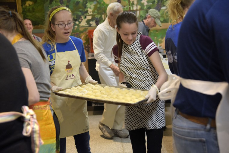 Ashley Theimer, 13, left, wearing her friend Ava's apron, and Ava Wolf, 12, right, carry a finished tray to another station. They came with Ava's mom, Elisa Wolf in the background left. Ava's grandmother, Maria Poppe, 74, who was raised in Little Italy and also volunteered, wants her grandchildren to learn the Italian traditions. (Algerina Perna/Baltimore Sun)