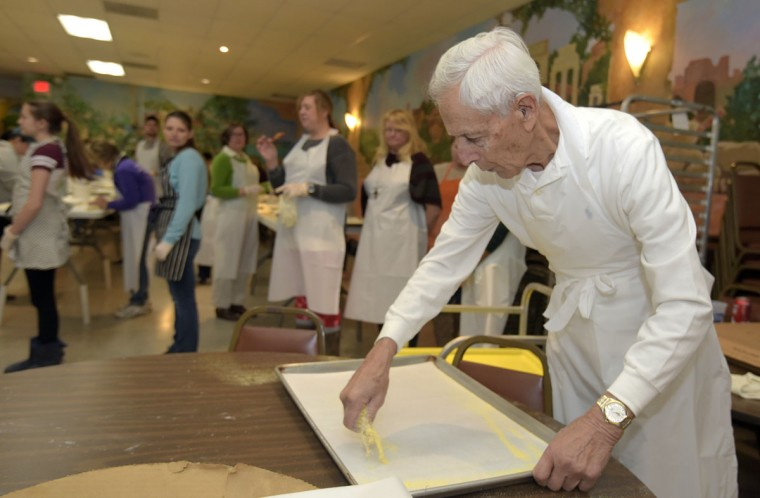 Vincent Rosso, 86, from Dundalk, spreads corn flour on the parchment paper to keep the raviolis from sticking. He has been volunteering in this job for 20 years. In the background, people stand in line waiting to get more dough from the rolling machine. (Algerina Perna/Baltimore Sun)