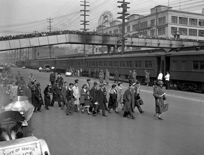 "A group of Bainbridge Island Japanese-Americans under army escort at a Seattle dock where they were entrained for the Manzanar, CA internment camp. Friends and relatives, soon to be ""evacuated,"" bid them farewell. Photograph, March 1942. U6343436ACME/CREDIT: BETTMANN-UPI"