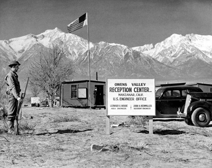 "Adding a military air, a sentry paces the boundary line of the Owens Valley Reception Center at Manzanar, CA, where thousands of Japanese were taken to live for the duration of World War II. The function of the Army was limited to transporting the ""evacuees"" and guarding the center. Photograph, March 24, 1942. U642532 ACME/CREDIT: BETTMANN-UPI"