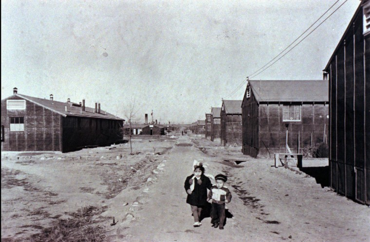 Two unidentified children walk alongside barracks housing at the Minidoka internment camp in Hunt, Idaho, circa 1943. Nearly 120,000 Japanese-Americans on the West Coast were forced into internment camps after Japan's attack on Pearl Harbor in December 1941. (AP Photo/ho-Wing Luke Asian Museum)