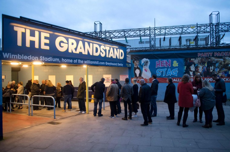Racegoers queue up outside Wimbledon Stadium ahead of an evening of greyhound racing in south London on March 18, 2017. March 25 will see the final day of racing at the Wimbledon dog track which will close to be demolished to make way for a new stadium for AFC Wimbledon. The closer of track will mark the end of the once hugely popular working-class sport of greyhound racing in London. (Justin Tallis/AFP/Getty Images)
