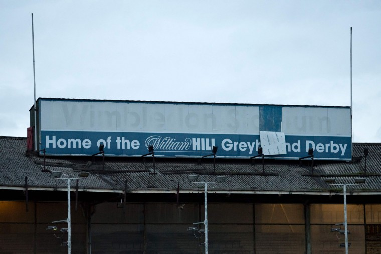 """A picture shows a worn sign that reads """"Wimbledon Stadium"""" inside Wimbledon Stadium ahead of an evening of greyhound racing in south London on March 18, 2017. March 25 will see the final day of racing at the Wimbledon dog track which will close to be demolished to make way for a new stadium for AFC Wimbledon. The closer of track will mark the end of the once hugely popular working-class sport of greyhound racing in London. (Justin Tallis/AFP/Getty Images)"""