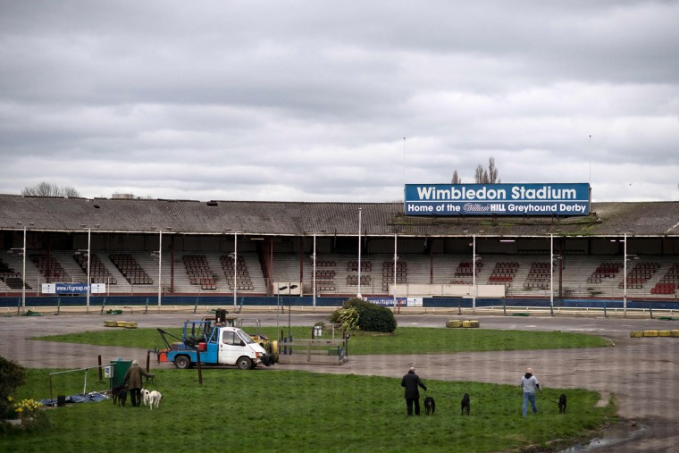 Trainers walk their animals around the inside of the track at Wimbledon Stadium ahead of an evening of greyhound racing in south London on March 18, 2017. March 25 will see the final day of racing at the Wimbledon dog track which will close to be demolished to make way for a new stadium for AFC Wimbledon. The closer of track will mark the end of the once hugely popular working-class sport of greyhound racing in London. (Justin Tallis/AFP/Getty Images)