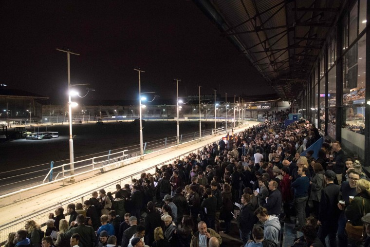 Racegoers wait ahead of another race during an evening of greyhound racing in south London on March 18, 2017. March 25 will see the final day of racing at the Wimbledon dog track which will close to be demolished to make way for a new stadium for AFC Wimbledon. The closer of track will mark the end of the once hugely popular working-class sport of greyhound racing in London. (Justin Tallis/AFP/Getty Images)