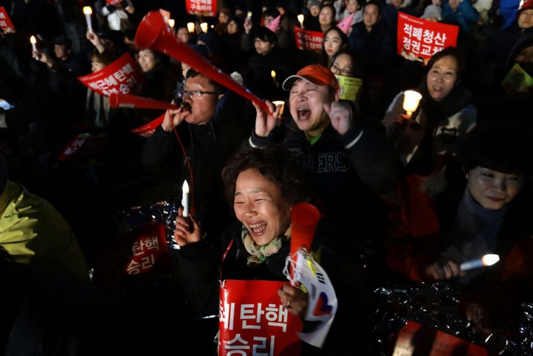 South Koreans celebrate after the Constitutional Court's verdict on March 10, 2017 in Seoul, South Korea. The Constitutional Court of South Korea upheld the impeachment of President Park Geun-hye on March 10, 2017. Park will be permanently removed from the South Korean office and the nation will need to hold a presidential election within 60 days. Park had been impeached by parliament in December for allegedly letting her confidante Choi Soon-sil involved in state affairs and colluded to take bribes of millions of dollars from South Korean conglomerates. (Photo by Chung Sung-Jun/Getty Images)