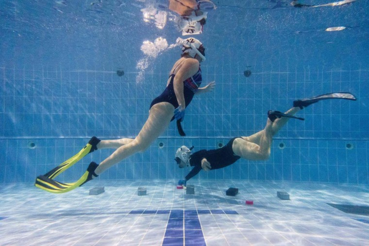 """In this photo taken on February 15, 2017, members of the """"HK Typhoon"""" underwater hockey club take part in training drills during their once-a-week team practice session at a 25-meter school pool in Hong Kong. The gravity defying sport of underwater hockey has gained a worldwide following -- now a Hong Kong team is diving in as the game takes off in Asia. (ANTHONY WALLACE/AFP/Getty Images)"""
