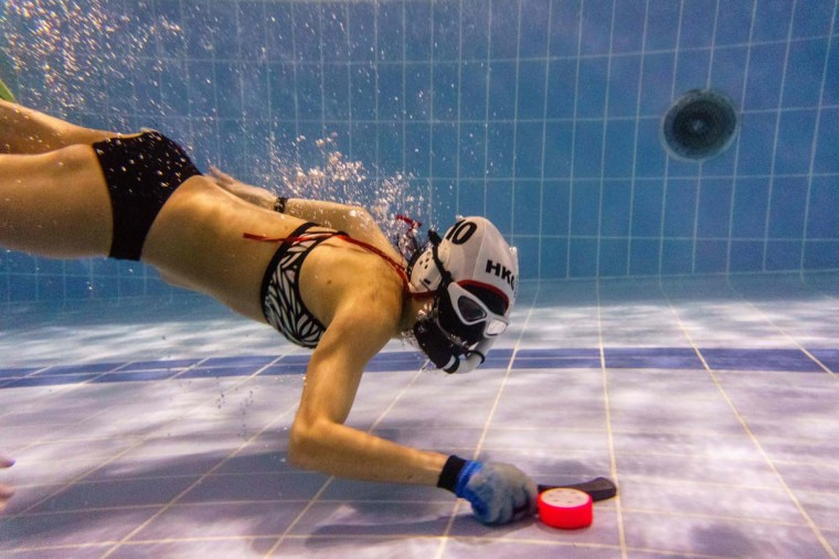 """In this photo taken on February 15, 2017, a member of the """"HK Typhoon"""" underwater hockey """"dribbles"""" the puck during the team's once-a-week team practice session at a 25-meter school pool in Hong Kong. The gravity defying sport of underwater hockey has gained a worldwide following -- now a Hong Kong team is diving in as the game takes off in Asia. (ANTHONY WALLACE/AFP/Getty Images)"""