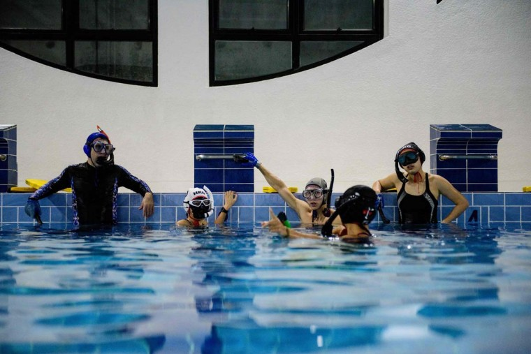 """In this photo taken on February 15, 2017, members of the """"HK Typhoon"""" underwater hockey club listen to a fellow player (second right) during their once-a-week team practice session at a 25-meter school pool in Hong Kong. The gravity defying sport of underwater hockey has gained a worldwide following -- now a Hong Kong team is diving in as the game takes off in Asia. (ANTHONY WALLACE/AFP/Getty Images)"""