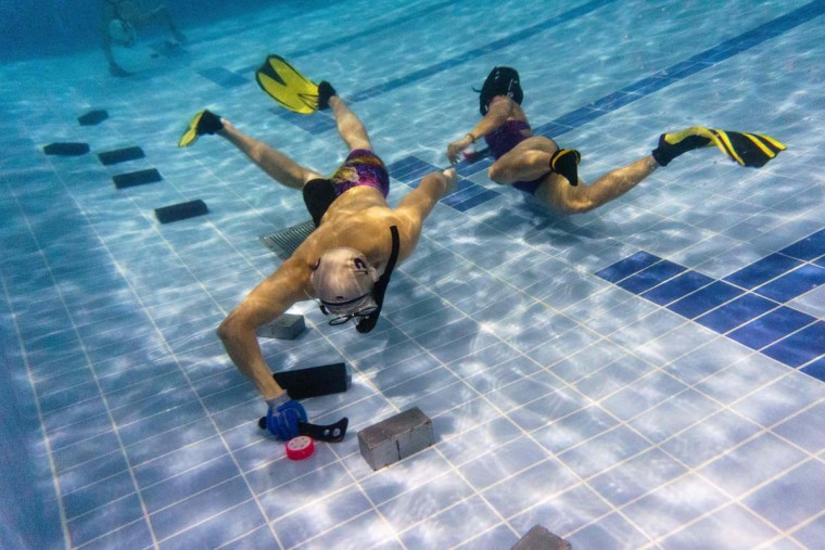 """In this photo taken on February 15, 2017, members of the """"HK Typhoon"""" underwater hockey club take part in exercise drills during the team's once-a-week practice session at a 25-meter school pool in Hong Kong. The gravity defying sport of underwater hockey has gained a worldwide following -- now a Hong Kong team is diving in as the game takes off in Asia. (ANTHONY WALLACE/AFP/Getty Images)"""