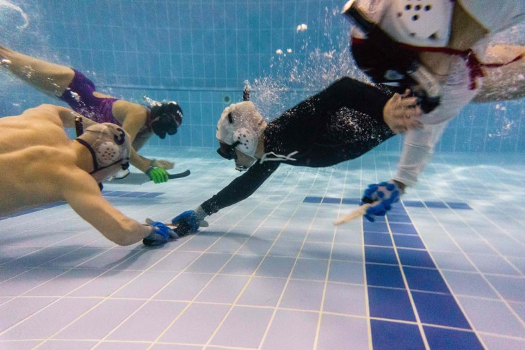 """In this photo taken on February 15, 2017, members of the """"HK Typhoon"""" underwater hockey club fight for possession of the puck during their once-a-week team practice session at a 25-meter school pool in Hong Kong. The gravity defying sport of underwater hockey has gained a worldwide following -- now a Hong Kong team is diving in as the game takes off in Asia. (ANTHONY WALLACE/AFP/Getty Images)"""
