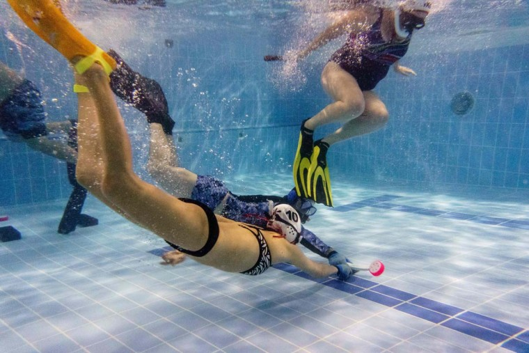 """In this photo taken on February 15, 2017, members of the """"HK Typhoon"""" underwater hockey club fight for possession of the puck (bottom right) during their once-a-week team practice session at a 25-meter school pool in Hong Kong. The gravity defying sport of underwater hockey has gained a worldwide following -- now a Hong Kong team is diving in as the game takes off in Asia. (ANTHONY WALLACE/AFP/Getty Images)"""