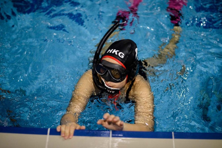 """In this photo taken on February 15, 2017, a member of the """"HK Typhoon"""" underwater hockey club completes a lap as she takes part in exercise drills during the team's once-a-week practice session at a 25-meter school pool in Hong Kong. The gravity defying sport of underwater hockey has gained a worldwide following -- now a Hong Kong team is diving in as the game takes off in Asia. (ANTHONY WALLACE/AFP/Getty Images)"""