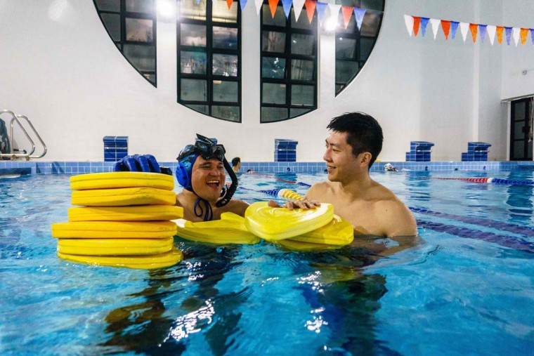 """In this photo taken on February 15, 2017, head coach Nowie Ignacio Cornelia (left), 37, from the Philippines, and geologist and former competitive swimmer Henry Chan (right), 28, who founded the """"HK Typhoon"""" underwater hockey club, chat after their once-a-week team practice session at a 25-meter school pool in Hong Kong. The gravity defying sport of underwater hockey has gained a worldwide following -- now a Hong Kong team is diving in as the game takes off in Asia. (ANTHONY WALLACE/AFP/Getty Images)"""