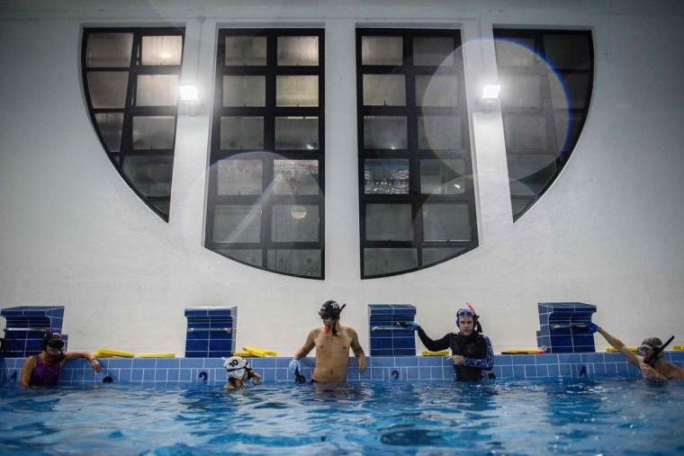 """In this photo taken on February 15, 2017, geologist and former competitive swimmer Henry Chan (center), 28, who founded the """"HK Typhoon"""" underwater hockey club, rests with his teammates during their once-a-week team practice session at a 25-meter school pool in Hong Kong. The gravity defying sport of underwater hockey has gained a worldwide following -- now a Hong Kong team is diving in as the game takes off in Asia. (ANTHONY WALLACE/AFP/Getty Images)"""