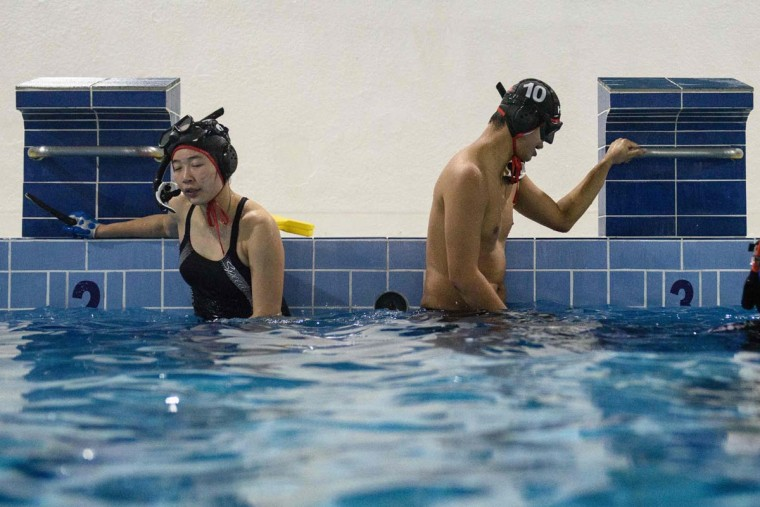 """In this photo taken on February 15, 2017, geologist and former competitive swimmer Henry Chan (right), 28, who founded the """"HK Typhoon"""" underwater hockey club, regains his breath with a teammate during their once-a-week team practice session at a 25-meter school pool in Hong Kong. The gravity defying sport of underwater hockey has gained a worldwide following -- now a Hong Kong team is diving in as the game takes off in Asia. (ANTHONY WALLACE/AFP/Getty Images)"""