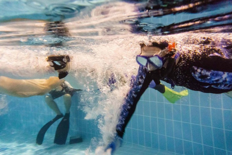 """In this photo taken on February 15, 2017, members of the """"HK Typhoon"""" underwater hockey prepare to dive for the puck during their once-a-week team practice session at a 25-meter school pool in Hong Kong. The gravity defying sport of underwater hockey has gained a worldwide following -- now a Hong Kong team is diving in as the game takes off in Asia. (ANTHONY WALLACE/AFP/Getty Images)"""
