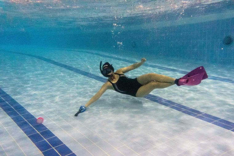 """In this photo taken on February 15, 2017, a member of the """"HK Typhoon"""" underwater hockey club reaches for the puck during the team's once-a-week practice session at a 25-meter school pool in Hong Kong. The gravity defying sport of underwater hockey has gained a worldwide following -- now a Hong Kong team is diving in as the game takes off in Asia. (ANTHONY WALLACE/AFP/Getty Images)"""