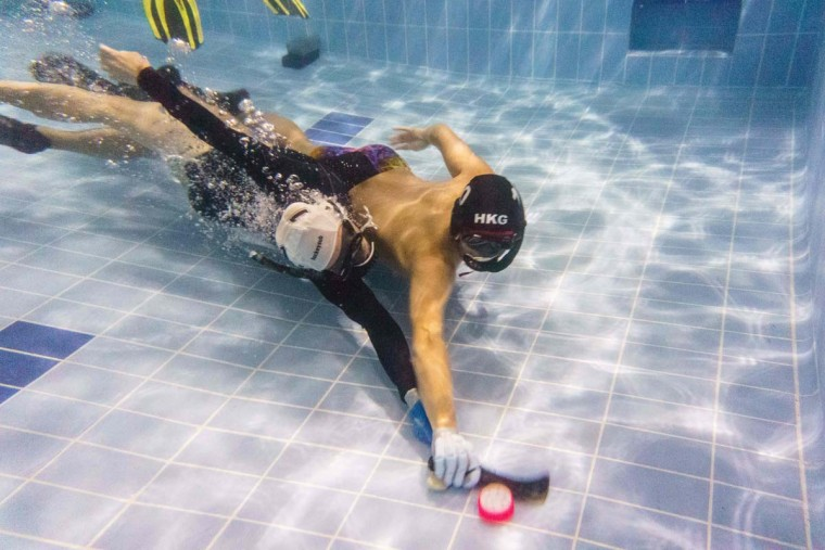 """In this photo taken on February 15, 2017, members of the """"HK Typhoon"""" underwater hockey club fight for possession of the puck (bottom center) during their once-a-week team practice session, at a 25-meter school pool in Hong Kong. The gravity defying sport of underwater hockey has gained a worldwide following -- now a Hong Kong team is diving in as the game takes off in Asia. (ANTHONY WALLACE/AFP/Getty Images)"""