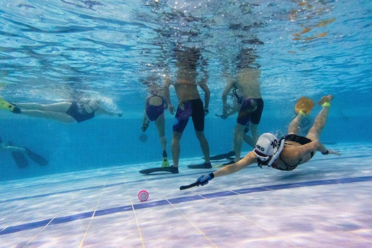"""In this photo taken on February 15, 2017, a member (right) of the """"HK Typhoon"""" underwater hockey reaches for the puck during their once-a-week team practice session at a 25-meter school pool in Hong Kong. The gravity defying sport of underwater hockey has gained a worldwide following -- now a Hong Kong team is diving in as the game takes off in Asia. (ANTHONY WALLACE/AFP/Getty Images)"""