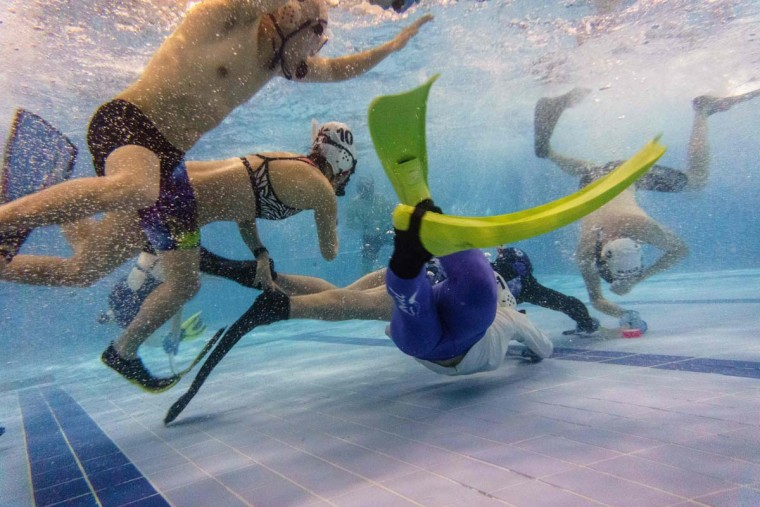 """In this photo taken on February 15, 2017, members of the """"HK Typhoon"""" underwater hockey club fight for possession of the puck (bottom right), during their once-a-week team practice session at a 25-meter school pool in Hong Kong. The gravity defying sport of underwater hockey has gained a worldwide following -- now a Hong Kong team is diving in as the game takes off in Asia. (ANTHONY WALLACE/AFP/Getty Images)"""