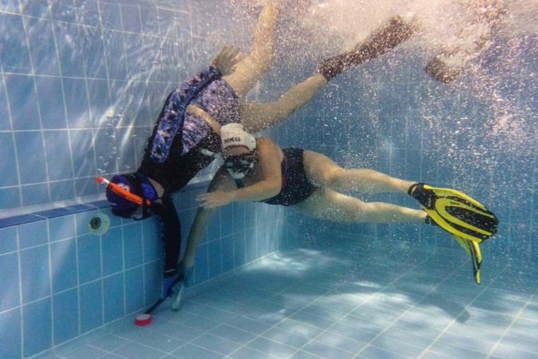 """In this photo taken on February 15, 2017, members of the """"HK Typhoon"""" underwater hockey club fight for possession of the puck (bottom left) during their once-a-week team practice session at a 25-meter school pool in Hong Kong. The gravity defying sport of underwater hockey has gained a worldwide following -- now a Hong Kong team is diving in as the game takes off in Asia. (ANTHONY WALLACE/AFP/Getty Images)"""