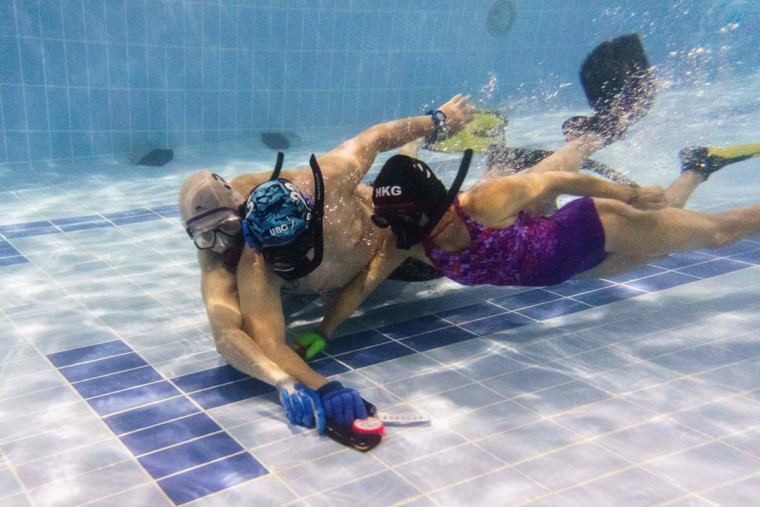 """In this photo taken on February 15, 2017, members of the """"HK Typhoon"""" underwater hockey club fight for possession of the puck (front center) during their once-a-week team practice session at a 25-meter school pool in Hong Kong. The gravity defying sport of underwater hockey has gained a worldwide following -- now a Hong Kong team is diving in as the game takes off in Asia. (ANTHONY WALLACE/AFP/Getty Images)"""