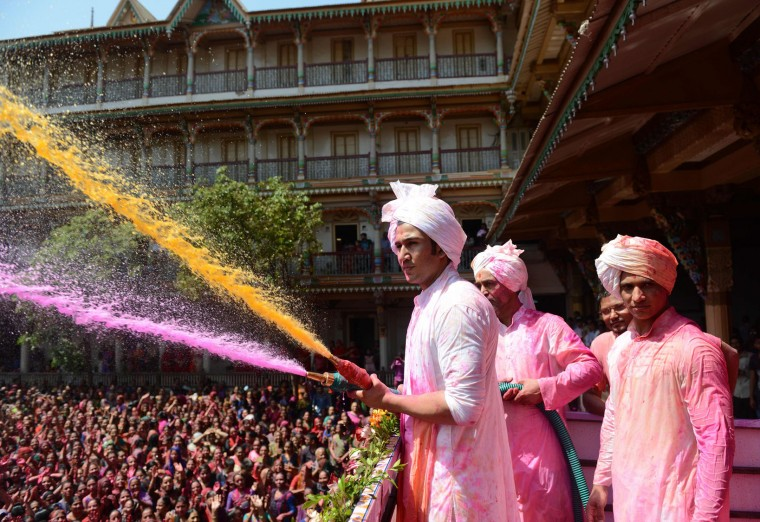 Indian heir to the Kalupur Swaminarayan Temple Lalji Maharaj Shri Vrajendraprasdaji Maharaj sprays Hindu devotees with coloured water as they celebrate the Holi festival at the Swaminarayan Temple in Ahmedabad on March 13, 2017. The Hindu festival of Holi, or the 'Festival of Colours' heralds the arrival of spring and the end of winter. (Sam Panthaky/AFP/Getty Images)