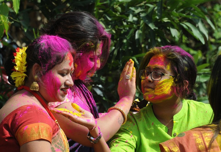 Indian revellers take part in celebrations for the Holi festival in Siliguri on March 12,2017. Holi marks the welcoming of spring and is a celebration of the triumph of good over evil, with people chasing each other and playfully splashing colorful paint, powder and water on each other. (Diptendu Dutta/AFP/Getty Images)
